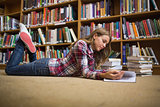 Young student lying on library floor reading