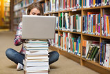 Young student sitting on library floor using laptop on pile of books