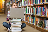 Happy student sitting on library floor using laptop on pile of books