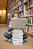 Smiling student sitting on library floor using laptop on pile of books