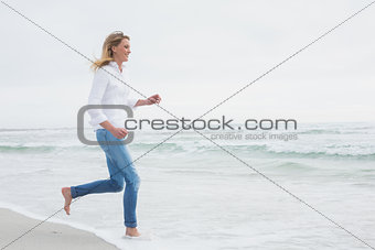 Side view of a woman running at beach