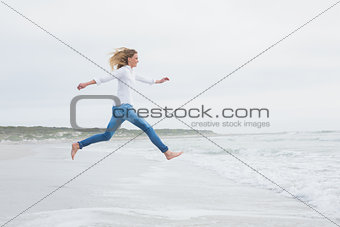 Side view of a casual woman jumping at beach