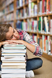 Napping student sitting on library floor leaning on pile of books