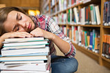 Dozing student sitting on library floor leaning on pile of books