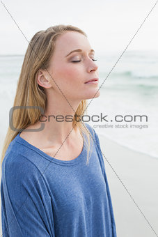 Casual woman with eyes closed at beach