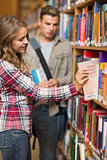 Pretty student taking book from shelf in library