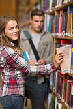 Smiling student taking book from shelf in library