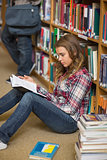 Focused student reading book on library floor