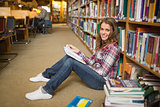 Smiling student reading book on library floor