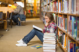 Pretty student reading book on library floor