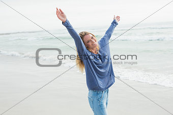 Happy woman standing with hands raised at beach