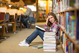 Pretty smiling student reading book on library floor
