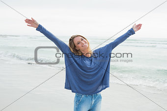 Happy woman with hands raised at beach