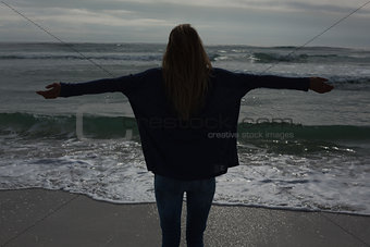 Silhouette rear view of woman with arms outstretched at beach