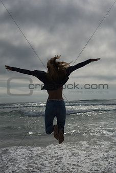 Full length rear view of a woman jumping at beach