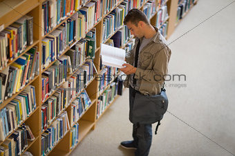 Student reading a book from shelf in library