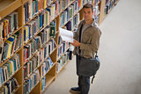 Student holding a book from shelf in library smiling at camera