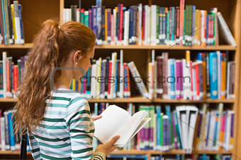 Redhead student reading book from shelf in library