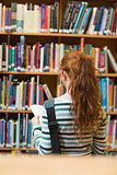 Redhead student reading book from shelf standing in library
