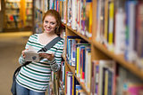 Smiling student reading book leaning on shelf in library