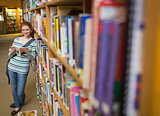 Cheerful student reading book leaning on shelf in library