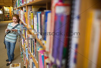 Focused student reading book leaning on shelf in library