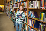 Focused student using tablet leaning on shelf in library