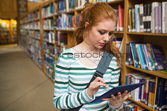 Focused student using tablet standing in library