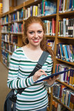 Smiling student using tablet standing in library