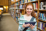 Cheerful student using tablet standing in library