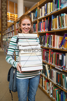 Cheerful student holding huge pile of books standing in library