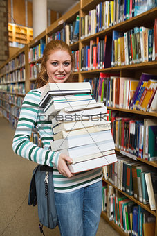 Cheerful student holding heavy pile of books standing in library