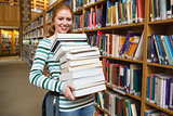 Smiling student holding heavy pile of books standing in library