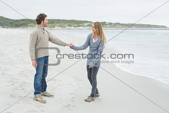 Side view of a couple holding hands at beach