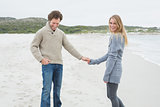 Happy young couple holding hands at beach