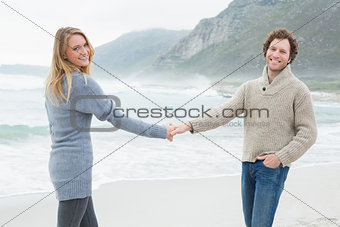 Casual happy couple holding hands at beach