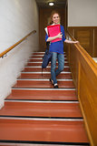 Smiling student holding folders on the stairs looking at camera