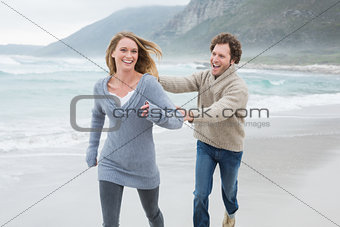 Cheerful couple running at beach