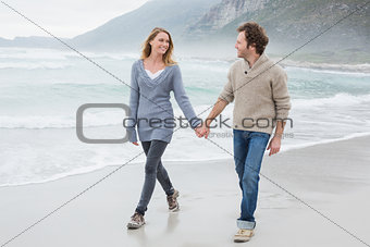 Couple holding hands and walking at beach