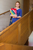 Cheerful student holding folders on the stairs looking at camera