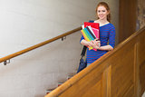 Redhead student holding folders on the stairs smiling at camera