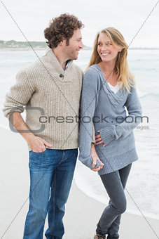 Couple holding hands and standing at beach