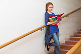 Redhead student reading notes on the stairs