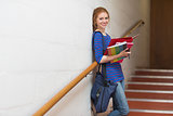 Smiling young student holding her notes on the stairs