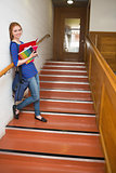 Happy young student holding her notes on the stairs