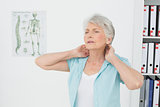 Senior woman suffering from neck pain in medical office