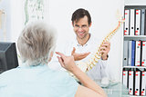 Friendly doctor explaining spine to a senior patient
