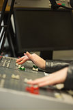 Student working on sound desk adjusting levels in the studio