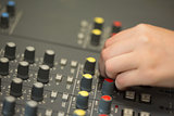 Hand working on a sound mixing desk