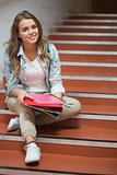 Happy student sitting on stairs looking at camera
